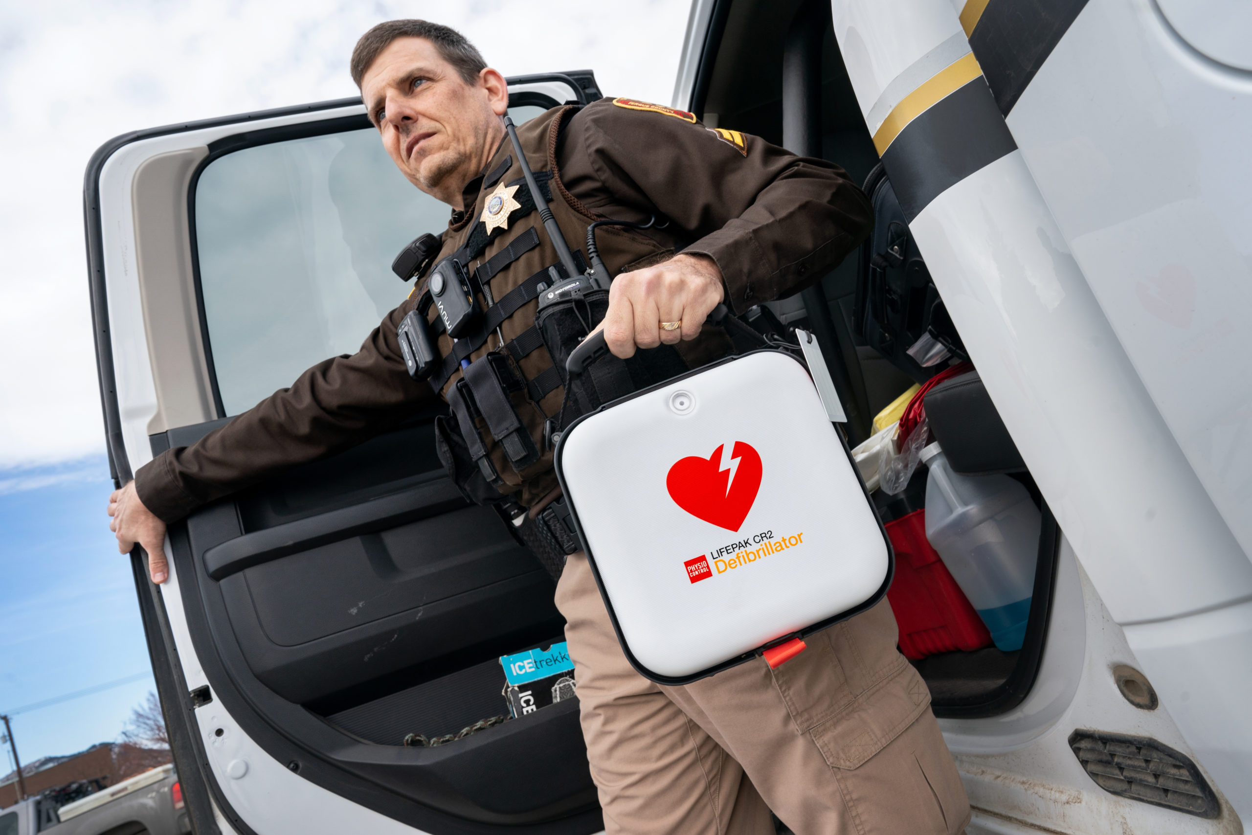 Show law enforcement officer with AED
